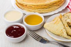 Les crêpes russes, confiture, miel, lait condensé, fourchette, ont plié le panca photographie stock