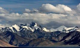 Les crêtes de montagne puissantes avec les crêtes couronnées de neige, nuages des rayures se trouvent sur des dessus de la montag Photo libre de droits
