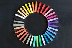 Les craies colorées alignées ont arrondi sur le cercle sur le backgro de tableau noir Images libres de droits