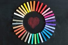 Les craies colorées alignées ont arrondi sur le cercle sur le backgro de tableau noir Photographie stock libre de droits