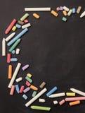Les craies dans un grand choix de couleurs ont arrangé sur un fond noir Photo libre de droits