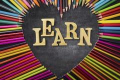 Les crayons colorés avec apprennent le mot Image stock
