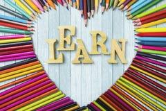 Les crayons colorés avec apprennent le texte Image libre de droits