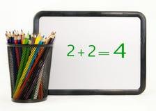 Les crayons colorés avec des maths sèchent le panneau d'effacement Image stock