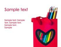 Les crayons colorés dans un sac rouge avec le coeur forment Photo stock