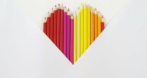 Les crayons colorés ont arrangé dans la forme de coeur sur le fond blanc banque de vidéos