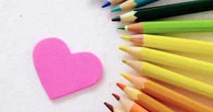 Les crayons colorés ont arrangé en semi cercle avec le coeur sur le fond blanc clips vidéos