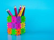 Les crayons de couleur dans coloré du support de crayon font le nombre de puzzle de forme sur le fond bleu Concept d'éducation Co Photos stock