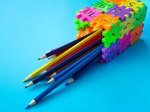 Les crayons de couleur dans le colorfull du support de crayon font le nombre de puzzle de forme sur le fond bleu Concept d'éducat Photographie stock