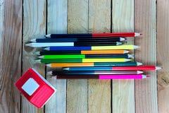 Les crayons de couleur et la petite maison sur la table en bois voient sur la vue supérieure Images stock