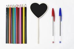 Les crayons en bois deux stylos et un petit tableau noir avec le coeur forment sur le fond blanc Images stock
