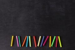 Les crayons en pastel lumineux se situent dans une rangée sur un conseil pédagogique noir Chil Images stock