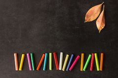 Les crayons en pastel lumineux se situent dans une rangée sur un conseil pédagogique noir Chil Images libres de droits