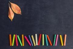 Les crayons en pastel lumineux se situent dans une rangée sur un conseil pédagogique noir Chil Photo stock