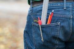 Les crayons, la boussole et les instruments de mesure dans des jeans arrières empochent photo stock