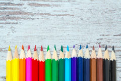 Les crayons multicolores colorés se ferment vers le haut du macro vers le bas sur un fond en bois de vintage, panneaux portés en  Photo stock