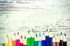 Les crayons multicolores colorés se ferment vers le haut du macro vers le bas sur un fond en bois de vintage, panneaux portés en  Images stock