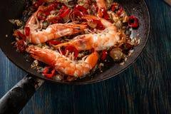 Les crevettes ont rôti sur la poêle à l'oignon, à l'ail et au piment Photo stock