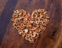 Les crevettes sèches se trouvent sur une table en bois sous forme de coeur photographie stock libre de droits