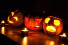 Les cric-o-lanternes effrayantes de potiron et de melon de Halloween sur le fond noir se sont allumées avec petit en rond et des  Photos libres de droits