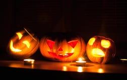 Les cric-o-lanternes effrayantes de potiron et de melon de Halloween sur le fond noir se sont allumées avec petit en rond et des  Images stock