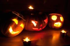 Les cric-o-lanternes effrayantes de potiron et de melon de Halloween sur le fond noir se sont allumées avec petit en rond et des  Image libre de droits