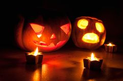 Les cric-o-lanternes effrayantes de potiron et de melon de Halloween sur le fond noir se sont allumées avec petit en rond et des  Photo stock