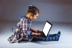Les cris fâchés de bébé se repose jouant l'ordinateur portable sur le gris Photographie stock libre de droits