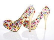 Les cristaux ont encroûté les chaussures d'or sur un backgro blanc Images libres de droits