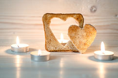 Les croûtons de pain sont parmi les bougies décoratives Un pain grillé avec du pain grillé en forme de coeur et deuxième est à an Photographie stock