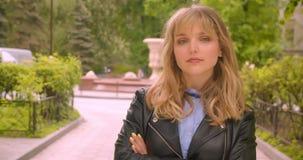 Les croix blondes caucasiennes joyeuses d'étudiant remet le coffre observant avec confiance dans la caméra en parc vert de ville banque de vidéos