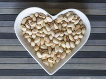 Les ?crous ont arrang? au coeur sur le fond Fin saine d'image de nourriture vers le haut des pistaches sur l'assiette creuse Text image libre de droits
