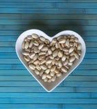 Les ?crous ont arrang? au coeur sur le fond Fin saine d'image de nourriture vers le haut des pistaches sur l'assiette creuse Text image stock
