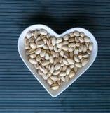 Les ?crous ont arrang? au coeur sur le fond Fin saine d'image de nourriture vers le haut des pistaches sur l'assiette creuse Text images libres de droits