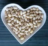 Les ?crous ont arrang? au coeur sur le fond Fin saine d'image de nourriture vers le haut des pistaches sur l'assiette creuse Text photos stock