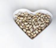 Les ?crous ont arrang? au coeur sur le fond Fin saine d'image de nourriture vers le haut des pistaches sur l'assiette creuse Text images stock