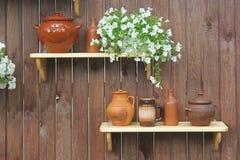 Les cruches et les pots de poterie se tiennent sur une étagère dans la perspective d'un mur en bois Photographie stock