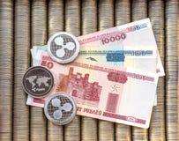 Les cryptos pièces de monnaie argentées ondulent XRP, rouble biélorusse de dénominations de papier Des pièces de monnaie en métal photos stock