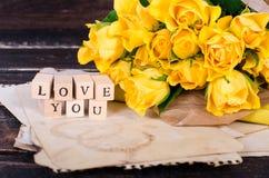 Les cubes en bois avec l'inscription AIMENT VOUS et le bouquet des fleurs jaunes sur le papier de vintage, fond en bois sélecteur Images stock