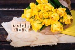 Les cubes en bois avec l'inscription AIMENT VOUS et le bouquet des fleurs jaunes sur le papier de vintage, fond en bois sélecteur Photo libre de droits