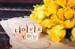 Les cubes en bois avec l'inscription AIMENT VOUS et le bouquet des fleurs jaunes sur le papier de vintage, fond en bois sélecteur Image stock