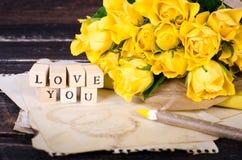 Les cubes en bois avec l'inscription AIMENT VOUS et le bouquet des fleurs jaunes sur le papier de vintage, fond en bois sélecteur Photos stock