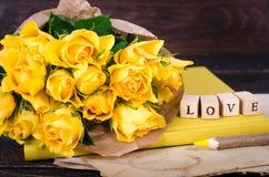 Les cubes en bois avec l'inscription AIMENT VOUS et le bouquet des fleurs jaunes sur le papier de vintage, fond en bois sélecteur Image libre de droits