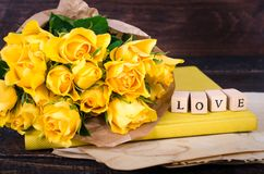 Les cubes en bois avec l'inscription AIMENT VOUS et le bouquet des fleurs jaunes sur le papier de vintage, fond en bois sélecteur Photo stock