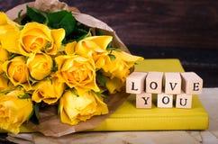 Les cubes en bois avec l'inscription AIMENT VOUS et le bouquet des fleurs jaunes sur le papier de vintage, fond en bois sélecteur Photographie stock