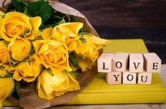 Les cubes en bois avec l'inscription AIMENT VOUS et le bouquet des fleurs jaunes sur le papier de vintage, fond en bois sélecteur Photos libres de droits