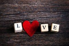 Les cubes en bois avec l'inscription aiment vous et le coeur rouge de textile sur le fond en bois L'espace libre pour votre texte Photos stock