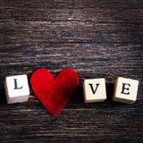 Les cubes en bois avec l'inscription aiment vous et le coeur rouge de textile sur le fond en bois L'espace libre pour votre texte Photos libres de droits