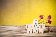 Les cubes en bois et sèchent les fleurs roses sur le nouveaux conseil en bois et toile de jute Image stock