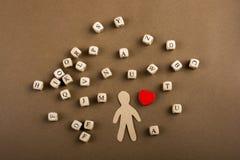 Les cubes en lettre et la figurine et le coeur en bois d'homme forment Photos libres de droits